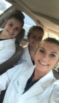 Students (from left to right) Leah Salzwedel, Addison Allen, and Maggie Jeffries smiling in their lab coats and uniforms.