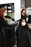hairdresser in a medical mask works in t
