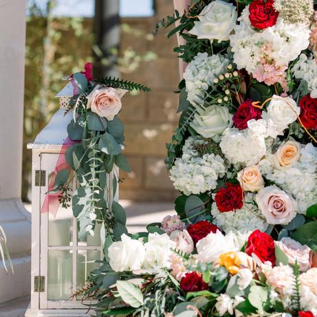 Lush wedding flowers adorning column @FazeliCellarsWeddings
