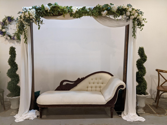Wood Archway w/ Swan lounge, chiffon draping and greenery silks