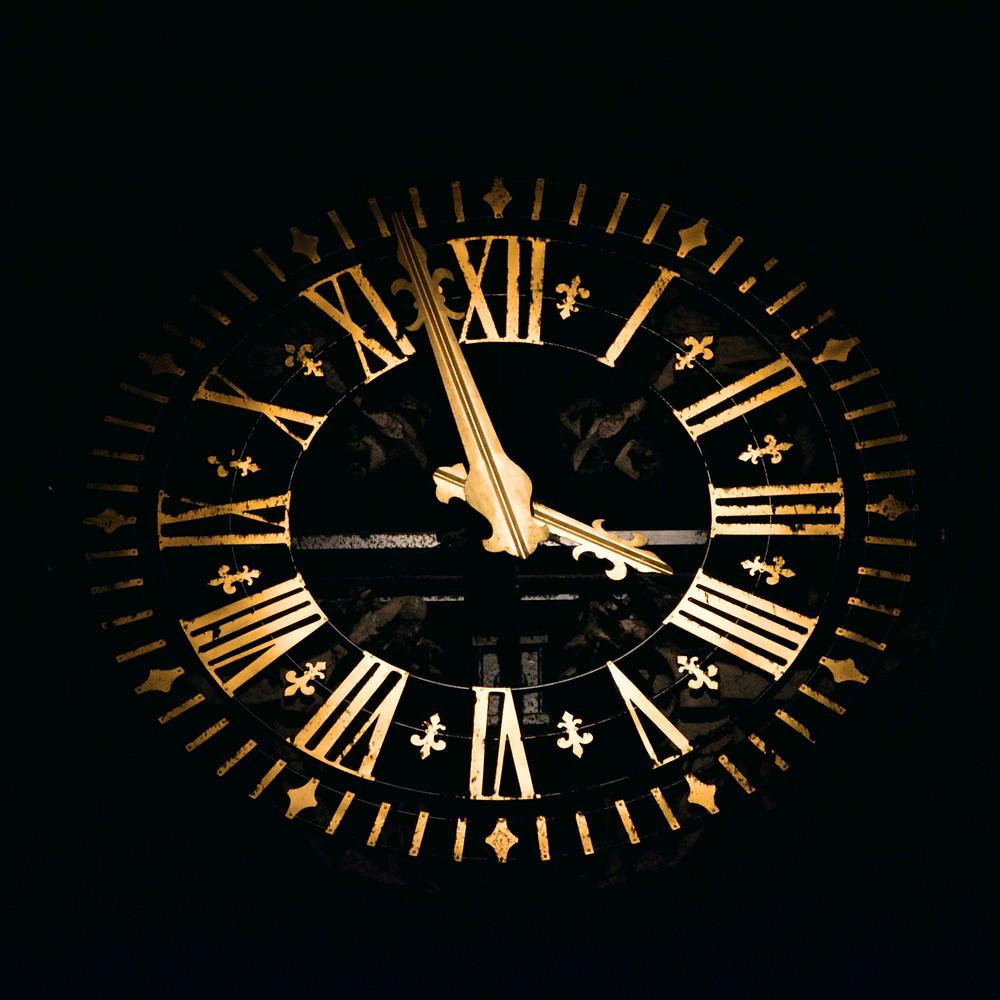 An clock face with gold Roman numerals against a black background.