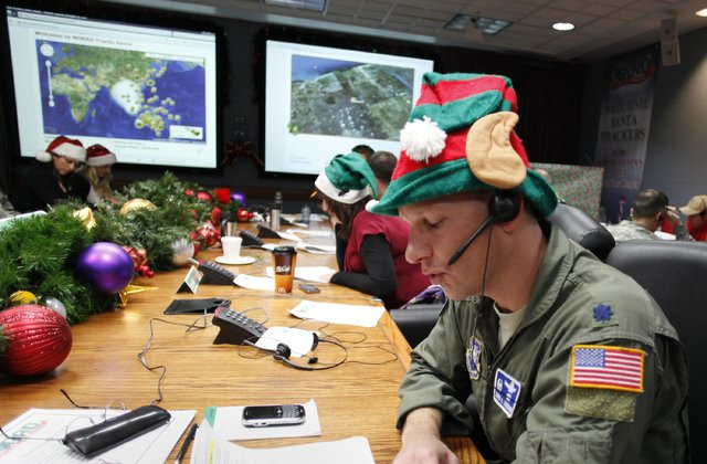 An Air Force Lieutenant Colonel wearing an elf hat and taking a call from a child at the NORAD Santa Tracker Operations Center.