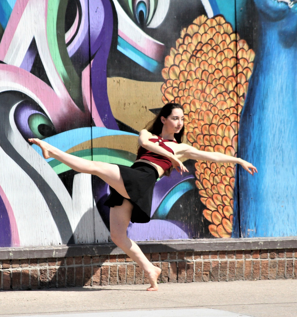 A woman in a maroon top and black skirt posing in front of a colorful mural on one foot with her other leg extended in front.
