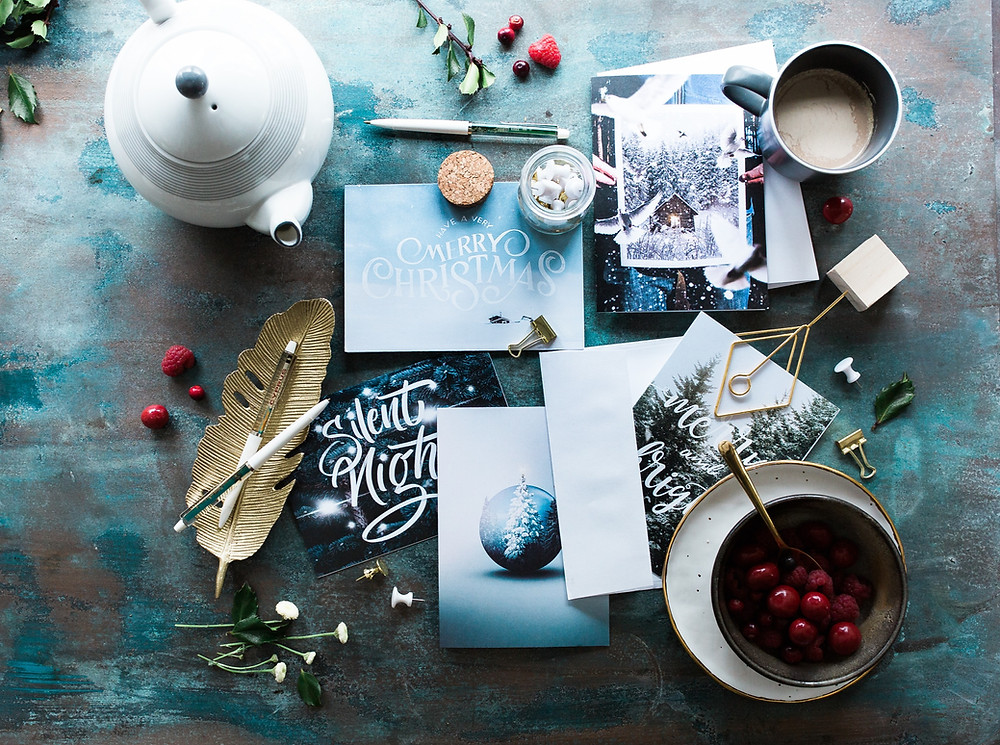 Assorted holiday cards on a wooden table with pens, a teapot, and a bowl of cranberries.