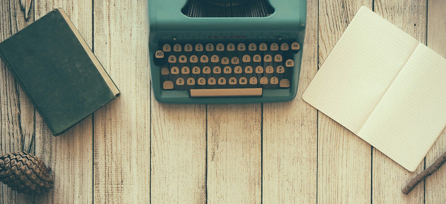 A wood table with a typewriter, book, notebook, and pinecone on top of it.
