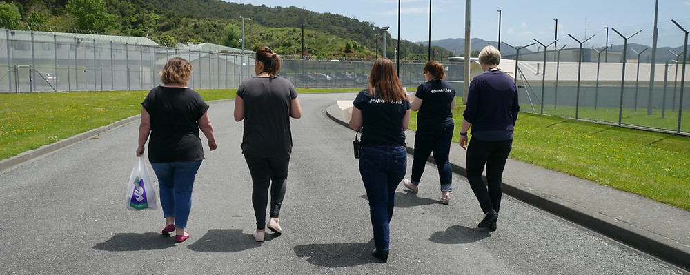 Five female Good Bitches walking down the prison drive way, with grass strips either side, between the prisonwire fences
