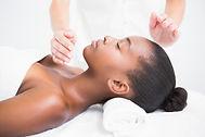 Pretty woman enjoying a reiki technique at the health spa.jpg