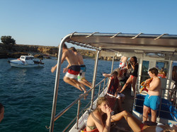 Kids jumping from boat into ocean