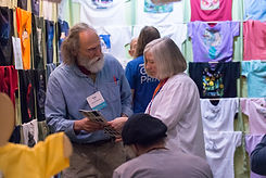 a buyer and an exhibitor discussing a catalog