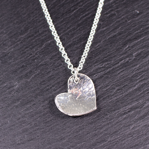 Hammered heart necklace on a slate background