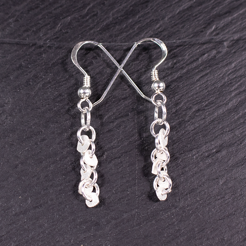 Silver mini disc earrings on slate background