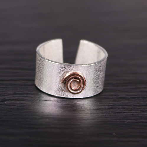 Textured adjustable silver ring with a copper spiral on a slate background