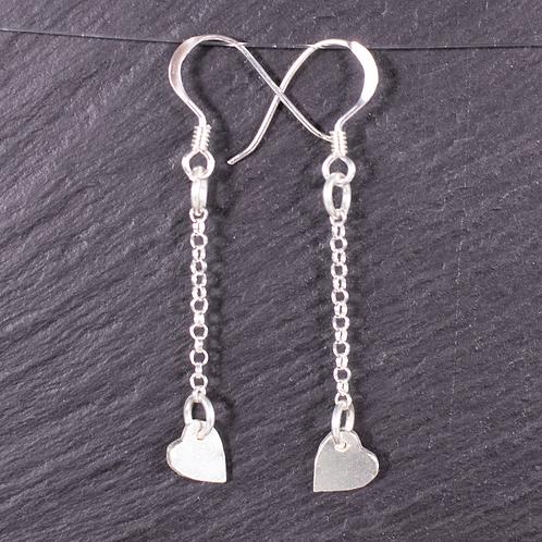 Silver long drop heart earrings on a slate background