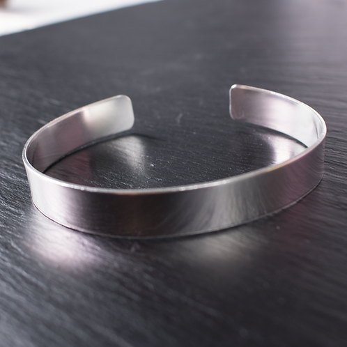 silver torque bangle on slate background
