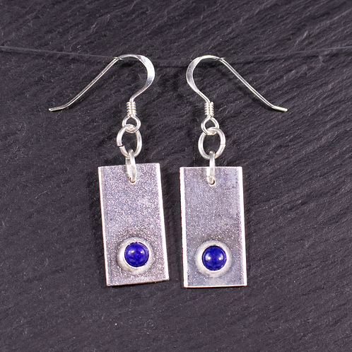 Silver rectangle earrings with a set lapis stone on slate background