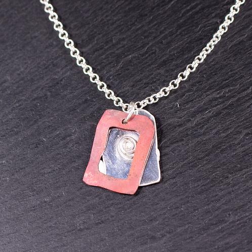 Silver necklace with copper frame necklace on a slate background
