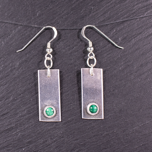 Silver rectangle earrings with a set malachite gemstone on a slate background