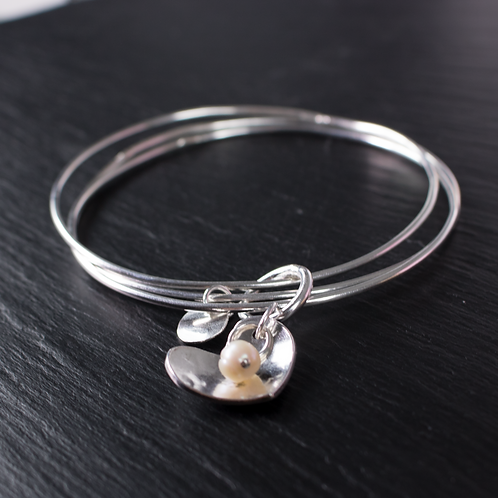 Triple loop bangle set with heart charm on slate background