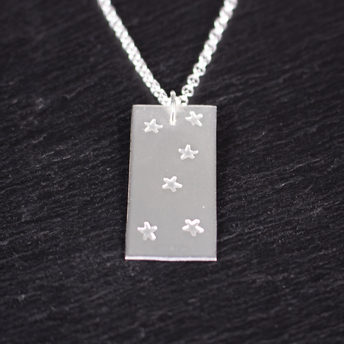 Silver star stamped necklace on slate background