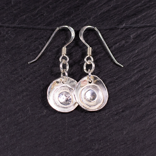 Frosted rose earrings on a slate background