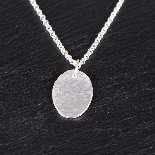 Silver hammered oval necklace on slate background
