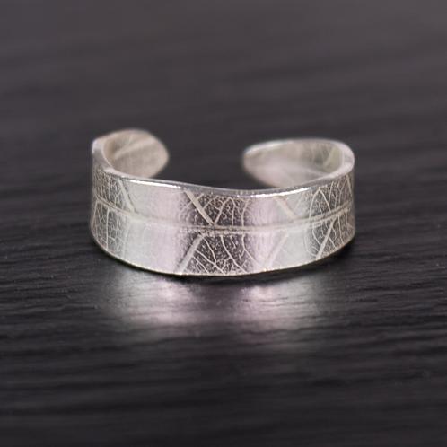 Silver leaf design ring on a slate background