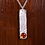Hammered necklace with amber stone on wood background