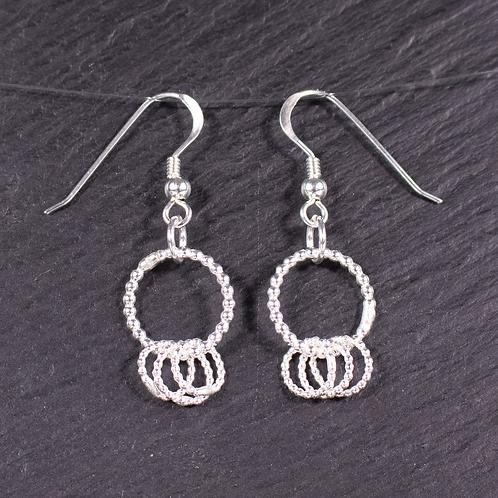Lovely loops silver earrings on a slate background