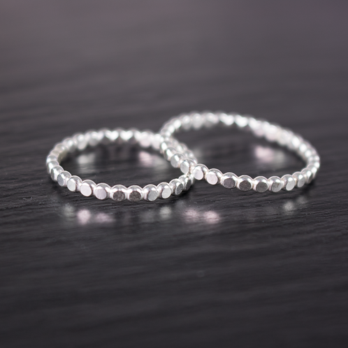 beaded wire silver rings on slate background
