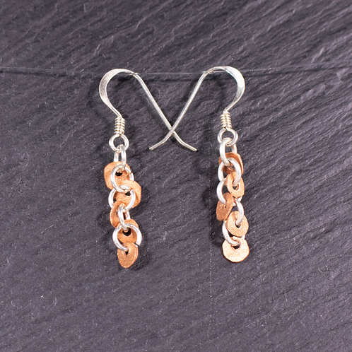 Copper drop earrings on a slate background