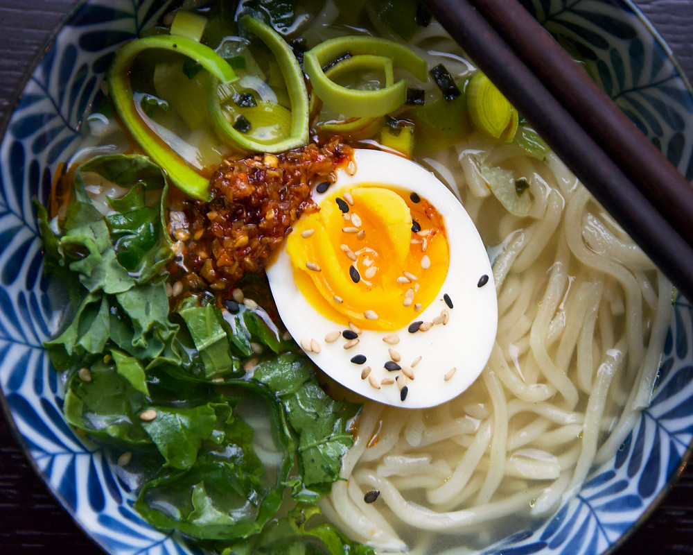 Overhead shot of Miso Leek Soup with half an egg, kale, chili paste and leeds.