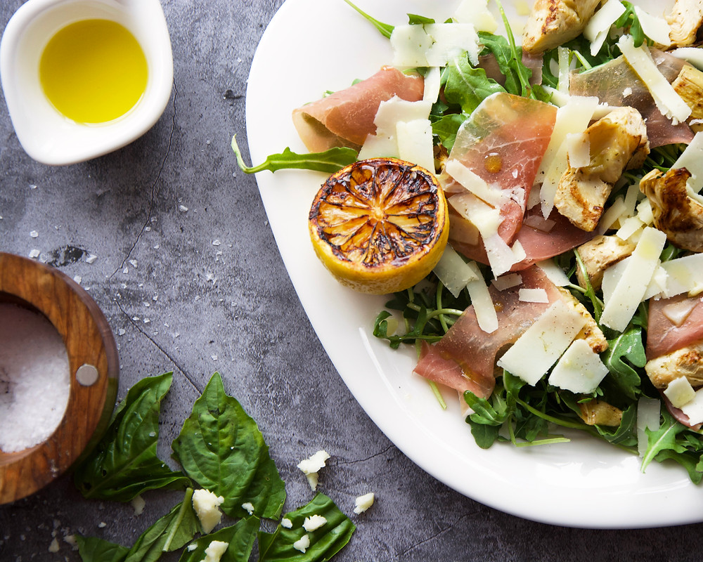 Overhead shot of salad with griddled artichokes, prosciutto, and pecorino shavings.