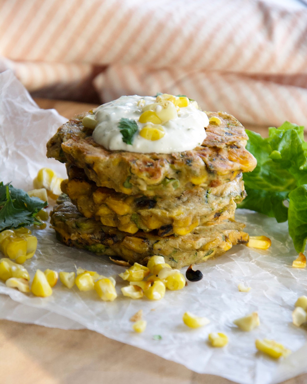 A stack of corn and zucchini fritters topped with a refreshing sour cream sauce.