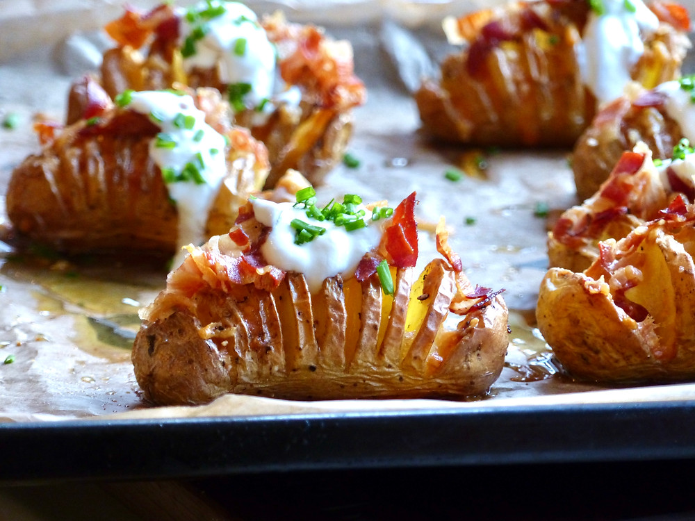 Hasselback potatoes, filled with melted parmesan, topped with crispy pancetta, a dollop of sour cream and chopped chives.