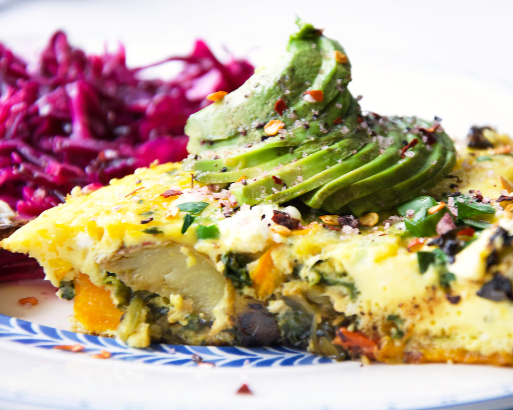 Close up of a slice of frittata with avocado slices and red cabbage in the background.