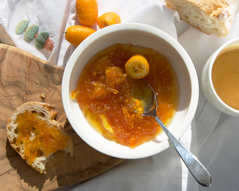 Flat lay of Kumquat Whiskey Marmalade with baguette slice and a coffee