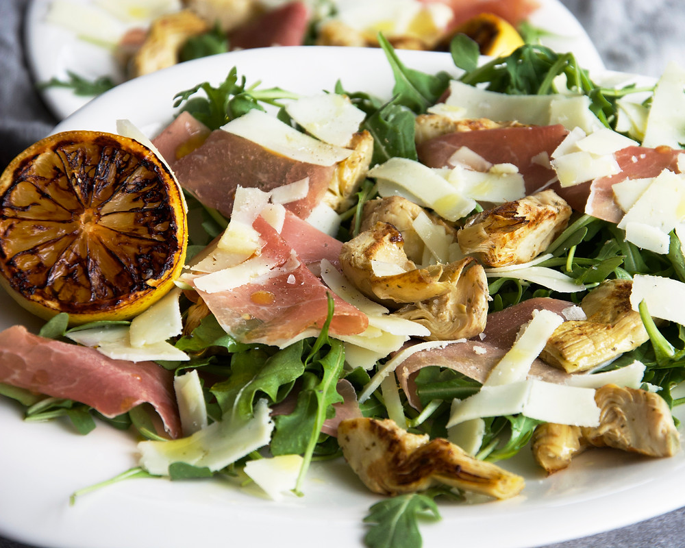 Close up of salad with griddled artichokes, prosciutto, and pecorino shavings.