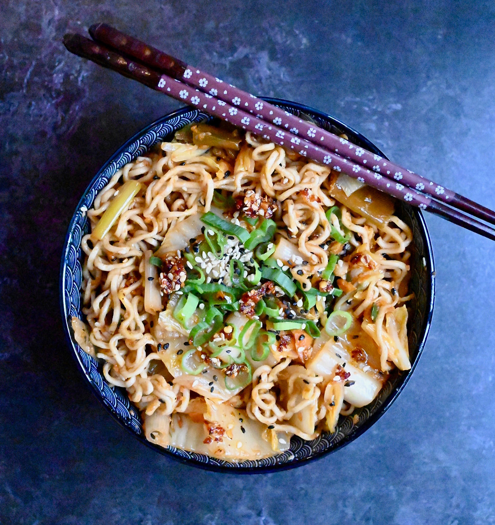 Noodles with kimchi, topped with green scallions, black and white sesame seeds and crispy garlic chili oil