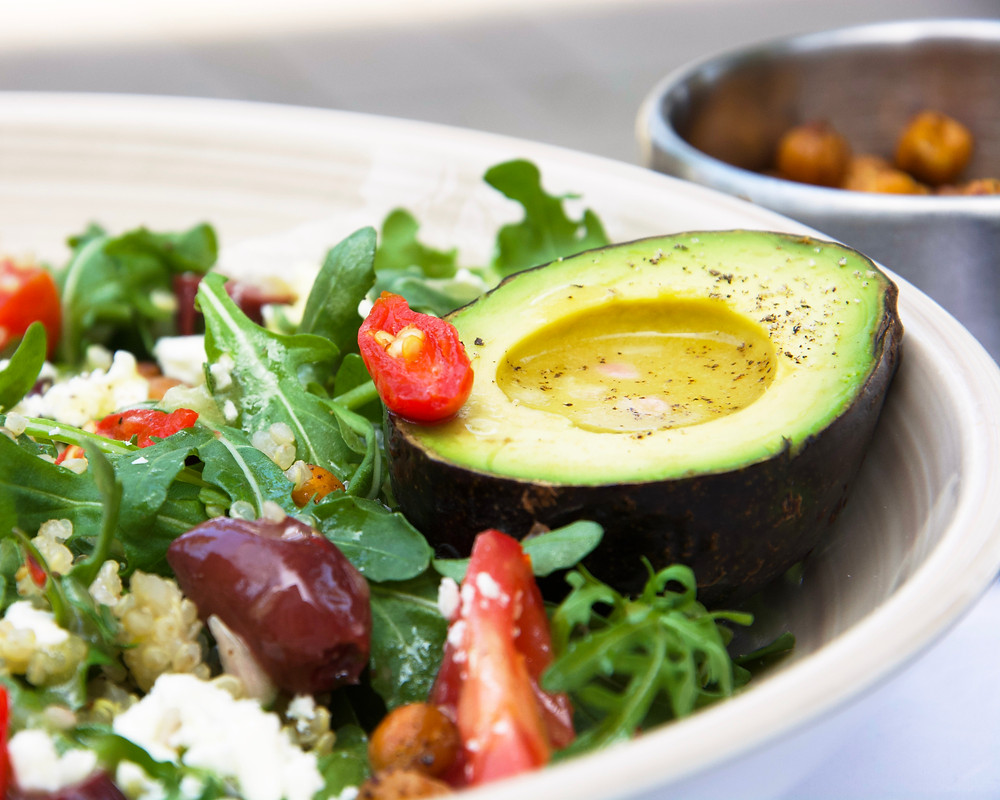 Close up of a bright salad with Mediterranean influences with arugula, quinoa, tomatoes, olives, pepper drops and avocado.