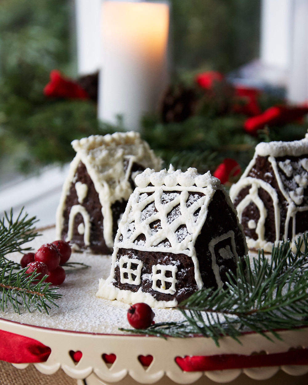 Mini Gingerbread Cake Village with Christmas candle in background.