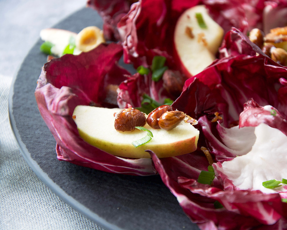 Close up of apple slice with caramelized hazelnuts on a bed of radicchio.