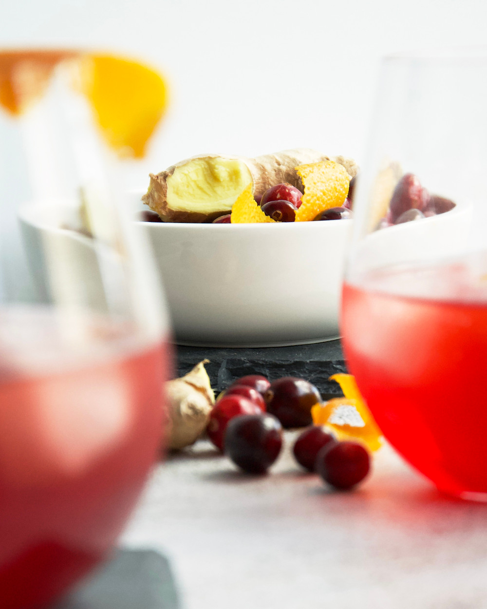 Focus on background of bowl of ginger and cranberries, blurred cocktails in foreground.