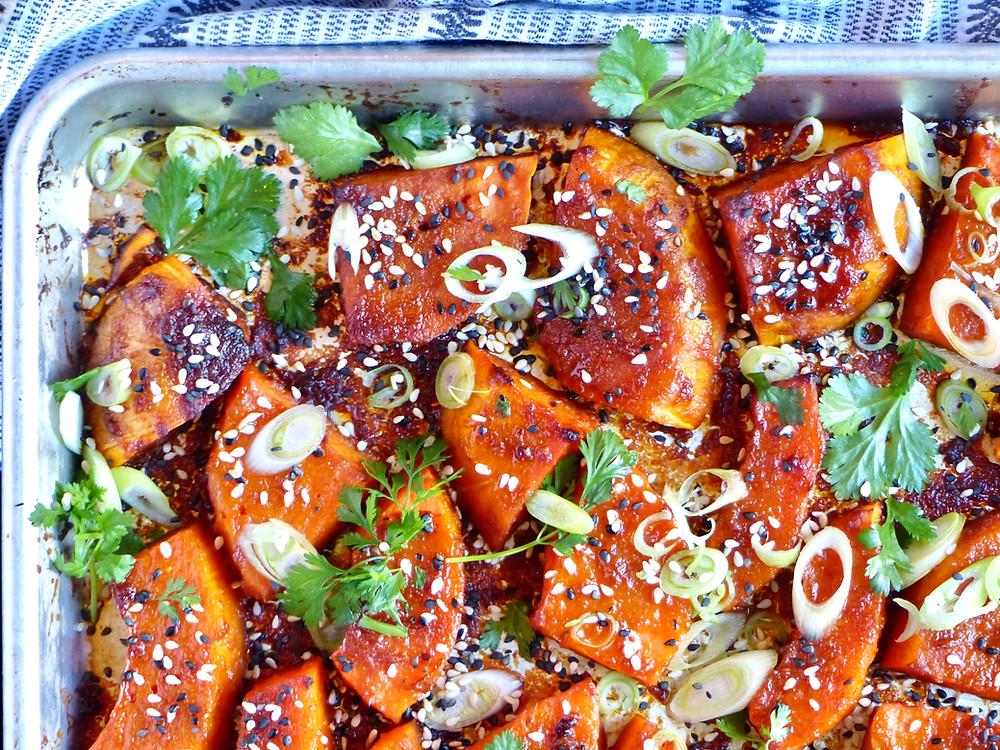 Roasted butternut squash seasoned with sesame oil, gochujang paste, soy sauce, garlic and ginger, garnished with cilantro, spring onions and sesame seeds.