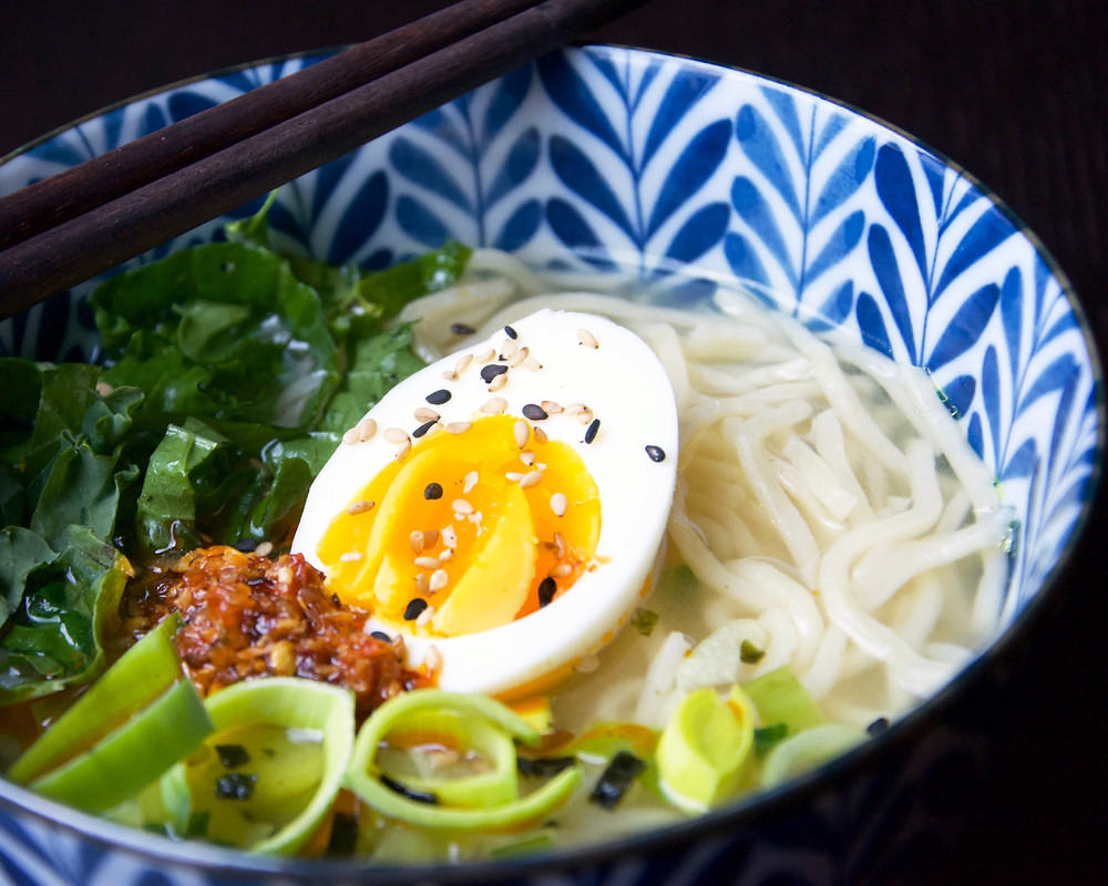 Close up of Miso Leek Soup with half an egg and udon noodles.