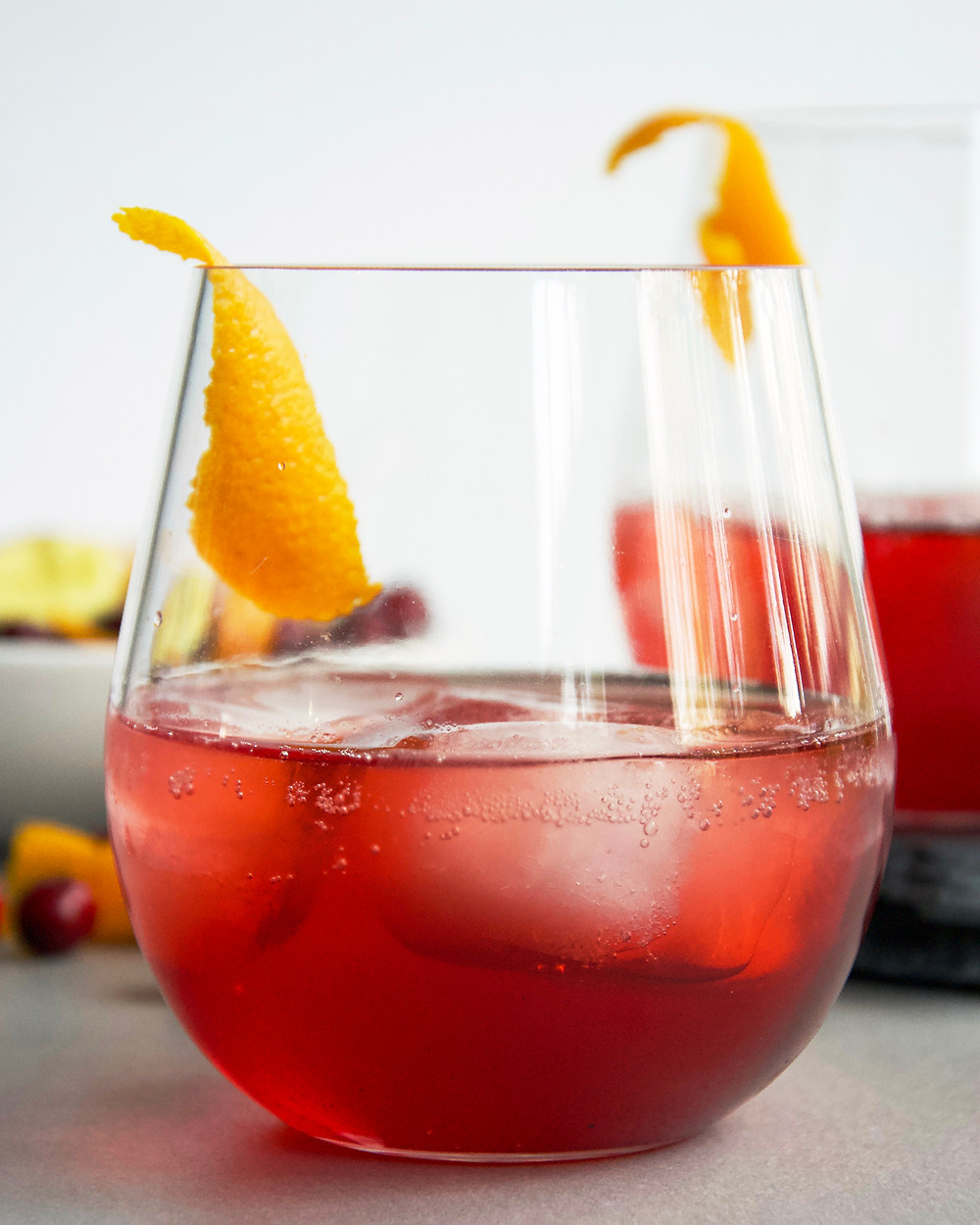 A close up of a light, in alcohol, cocktail with cranberry juice, Aperol and a hint of ginger.
