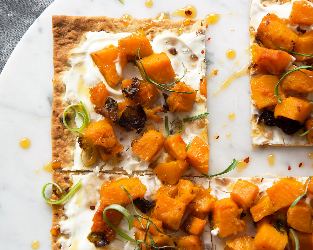 Overhead shot of flat bread with butternut squash and goat cheese cream.