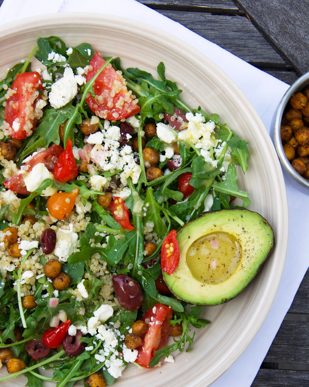 A bright salad with Mediterranean influences with arugula, quinoa, tomatoes, olives, pepper drops and avocado.