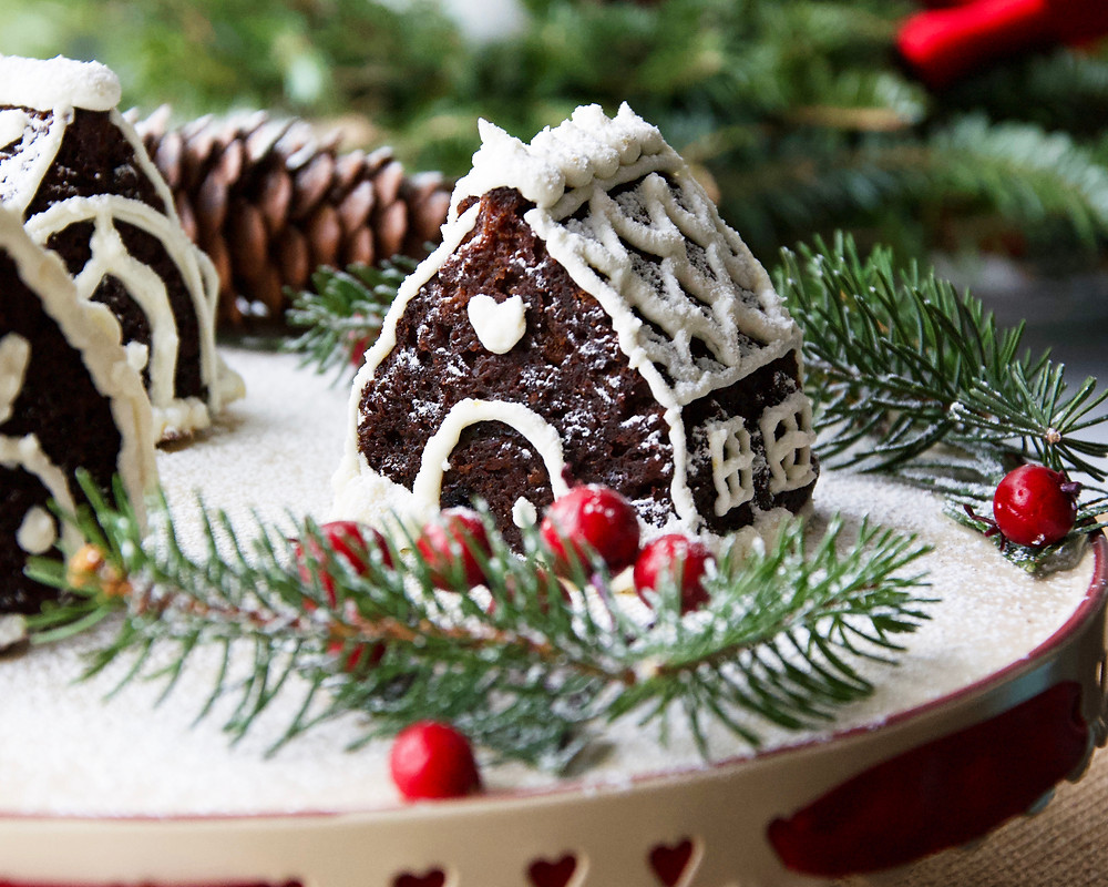 Mini Gingerbread Cake House with Grand Marnier Cream Cheese Frosting, nestled amongst Christmas decorations.