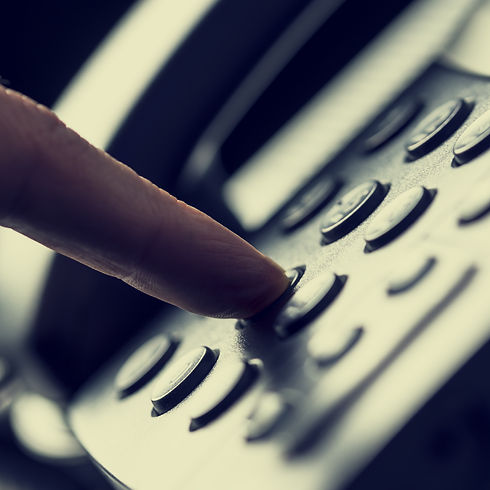 Retro image of a finger pressing a number button on the telephone to make a call.jpg