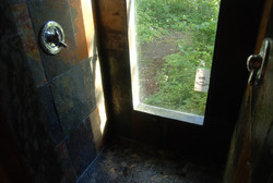 Double shower with slate and rock flooringwith window to the woods